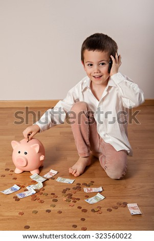 Happy boy sitting on the floor, collecting money in his piggy bank and talking phone - stock photo
