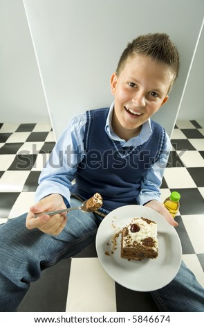 Happy boy sitting on the floor with cake on dessert plate. Looking at camera.