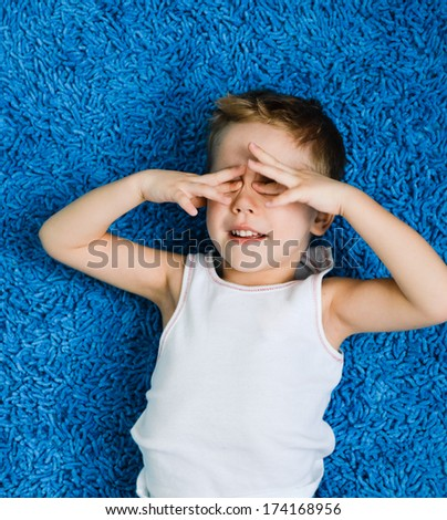 Happy boy sleepy kid on blue carpet in living room at home - stock photo