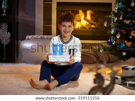 Happy boy smiling, holding christmas present, sitting on floor by christmas tree. - stock photo