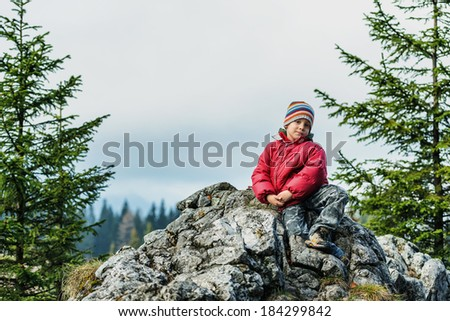 Happy boy standing on a cliff admiring nature