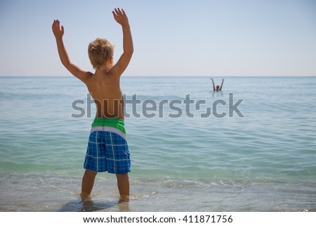 Happy boy standing on the ocean shore on a sunny day. Child going to swim in the sea. Vacations. Activities for child on the beach. Joy and happiness. - stock photo
