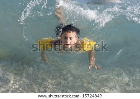 Happy boy swimming in sea - stock photo