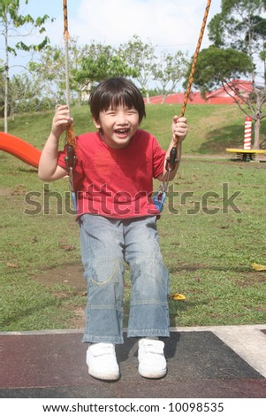 Happy boy swinging happily at the playground in the park - stock photo