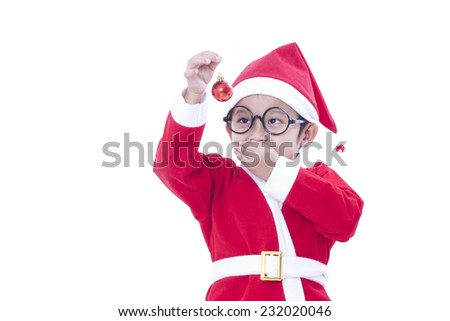 Happy boy wearing santa claus uniform and holding red christmas ball  - stock photo