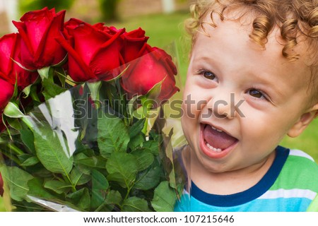 happy boy with a bouquet of red roses - stock photo
