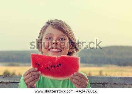 Happy boy with a slice of watermelon in his hands. - stock photo