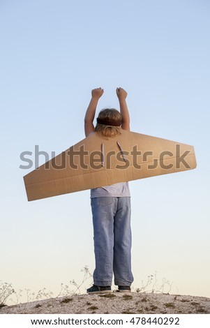 Happy boy with cardboard boxes of wings against the sky dream of flying