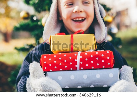 Happy boy with Christmas gifts - stock photo