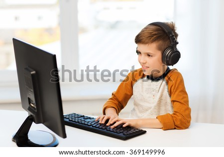 happy boy with computer and headphones at home