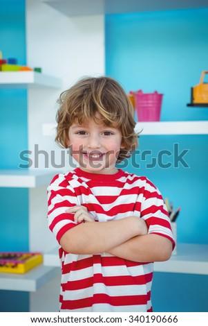 Happy boy with folded arms beside a shelf - stock photo
