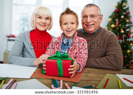 Happy boy with gift-box looking at camera with his grandparents near by - stock photo