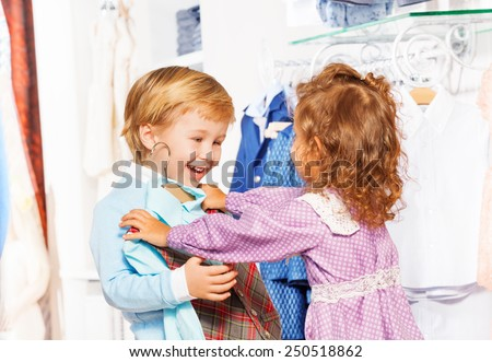Happy boy with girl who fits on him vest in store