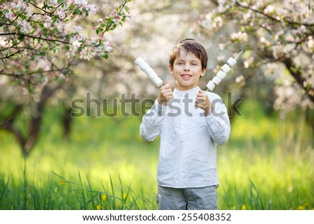 Happy boy with marshmallow on sticks in blooming garden - stock photo