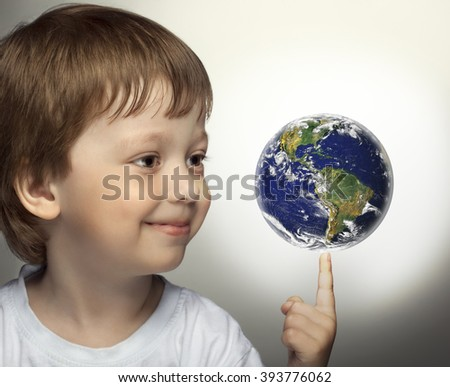 happy boy with planet Earth in hand. Elements of this image furnished by NASA.