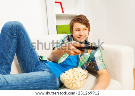 Happy boy with popcorn relaxing on white sofa - stock photo