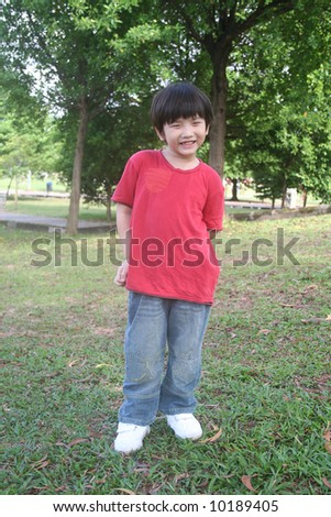 Happy boy with red t-shirt and jeans at the park - stock photo