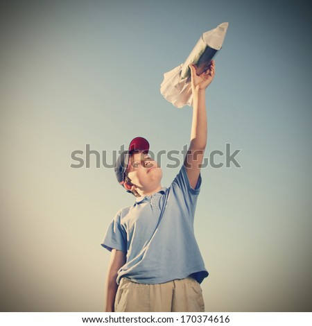 Happy boy with rocket outdoors play - stock photo