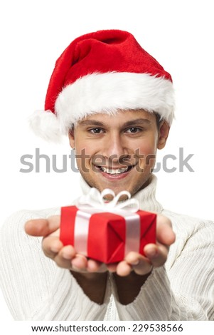 Happy boy with santa hat holding a gift - stock photo