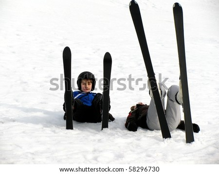 Happy boy with ski on lying in the snow and pauses - stock photo