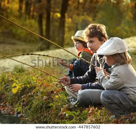 happy boys go fishing on the river - stock photo