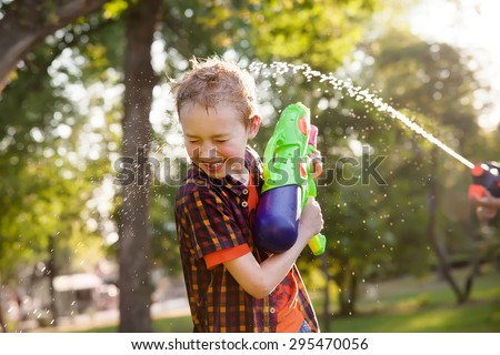 happy boys playing with water guns - stock photo
