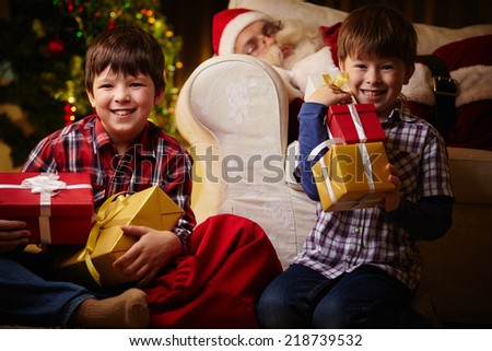 Happy boys with giftboxes looking at camera on background of sleeping Santa Claus - stock photo