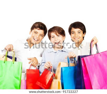 Happy boys with gifts, kids carrying colorful shopping bags with Christmas presents isolated over white background, holidays