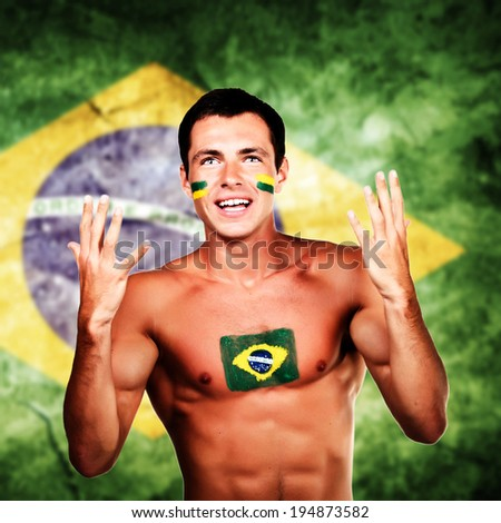 Happy brazilian fan over brazil flag background - stock photo