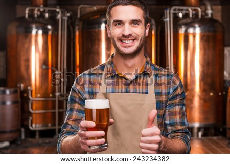 Happy brewer. Happy young male brewer in apron holding glass with beer and looking at it with smile while standing in front of metal containers - stock photo