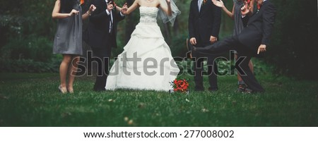 Happy bridal couple with guests  in garden. Summer wedding picture. - stock photo