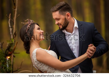 happy bride and bearded groom are dancing in the autumn forest - stock photo