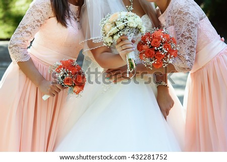 happy bride and bridesmaids showing their luxury bouquets at gorgeous wedding reception - stock photo