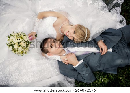 Happy bride and groom are lying on green grass - stock photo