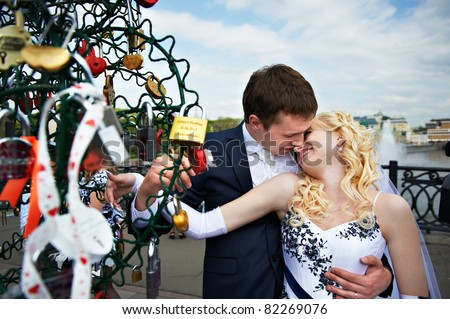 Happy bride and groom at wedding walk on Luzhkov bridge in Moscow