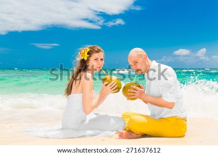 Happy bride and groom drink coconut water and having fun on a tropical beach. Wedding and honeymoon on the tropical island. - stock photo