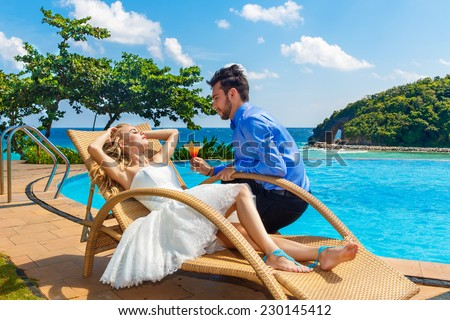 happy bride and groom enjoy a cocktail poolside infinity. Tropical sea in the background. - stock photo