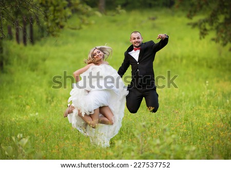 Happy bride and groom enjoying their wedding day in green nature - stock photo