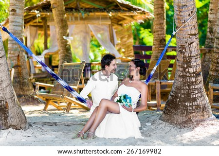 Happy bride and groom having fun in a hammock on a tropical beach under the palm trees. Summer vacation concept. - stock photo