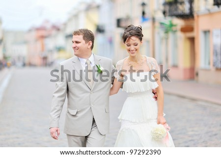 Happy bride and groom having fun in an old town - stock photo