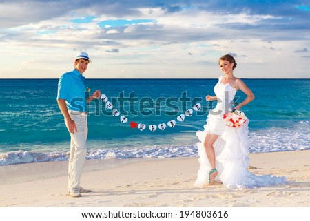 Happy bride and groom having fun on a tropical beach. Just married. - stock photo
