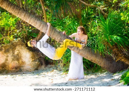 happy bride and groom having fun on a tropical jungle - stock photo