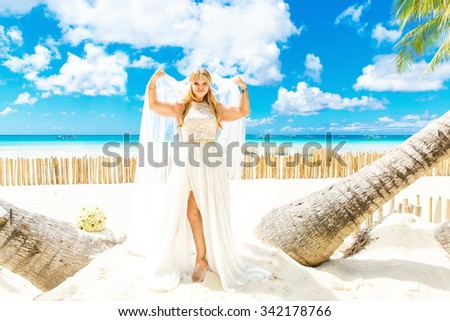 Happy Bride and Groom having fun on the tropical beach under the palm trees. Wedding and honeymoon concept.