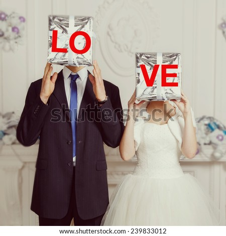 Happy bride and groom holding LOVE. Bride and groom, original wedding. Wedding, love, groom, bride, gift, day, gift box - holiday concept. Original wedding, bride and groom cover their faces gift. - stock photo