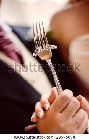 Happy Bride and Groom Holding wedding bands on a silver fork - stock photo