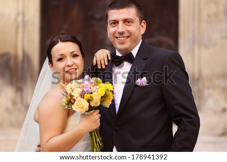 Happy bride and groom in front of church
