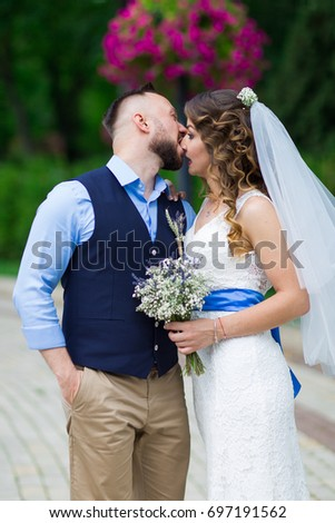 Happy bride and groom in park. Beautiful couple in Wedding day. Beautiful bride and elegant groom after wedding ceremony. Happy couple Marriage. The guy kisses the girl / Lovers /  Funny photo