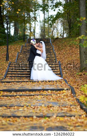 Happy bride and groom in yellow autumn foliage on wedding walk - stock photo