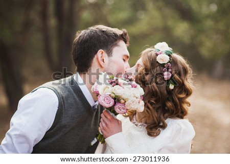happy bride and groom kissing in spring park. wedding couple in love. wedding reception. portrait of man, woman. newlyweds. happy bride and groom on their wedding ceremony. bridal bouquet of flowers - stock photo