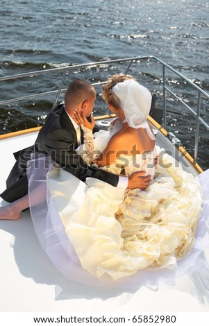 Happy bride and groom on a luxury yacht at ocean in a sunny day - stock photo